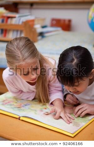 schoolgirls reading a fairy tale together in a classroom stock photo © wavebreak_media