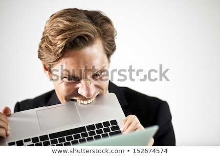 Man biting a laptop in frustration Stock photo © Rugdal