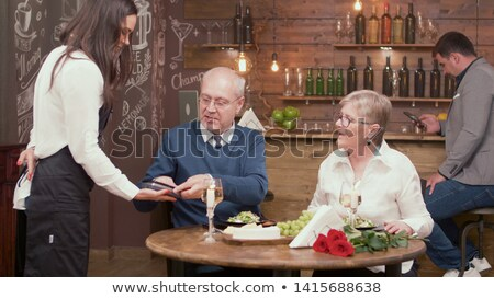 Happy couple in restaurant pay for their meal Stock photo © HASLOO