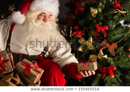Santa putting gifts under Christmas tree in dark room Stock photo © HASLOO