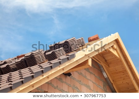 Stockfoto: Tiler Covering Roof With New Tile