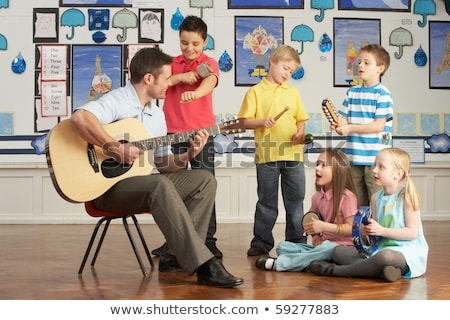 male teacher playing guitar with pupil in classroom stock photo © monkey_business