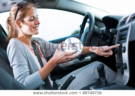 Young female driver playing music in the car (changing CDs) Stock photo © lightpoet