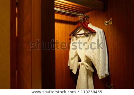 Bathrobes with wooden hangers in hotel wardrobe Stock photo © punsayaporn