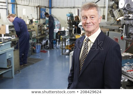 Stok fotoğraf: Owner Of Engineering Factory With Staff In Background