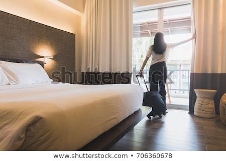 Joli dame chambre d'hôtel séance lit maison Photo stock © eleaner