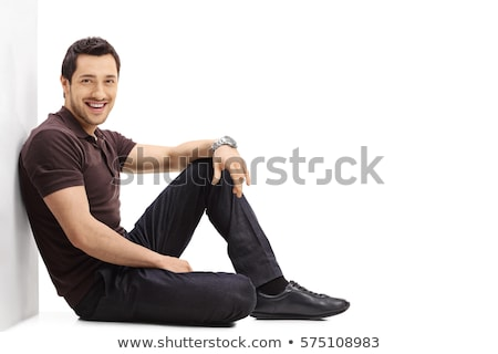 casual man sitting and leaning on a white wall stock photo © feedough
