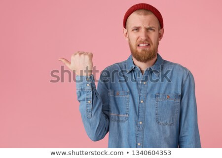 Disgusted man with beard makes face at camera Stock photo © ozgur