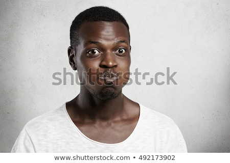 Funny african man closed one eye and looking at camera Stock photo © deandrobot