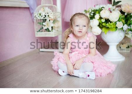 little girl ballerina sitting with legs crossed in ballet studio stock photo © deandrobot