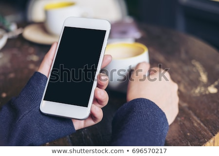morning coffee drink and mobile phone in female hands stock photo © stevanovicigor