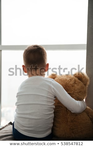 Stock photo: Little boy with teddy bear near window waiting for parents