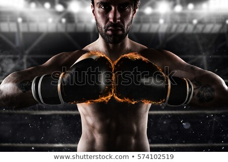 Foto stock: Confident Boxer With Fiery Boxing Gloves
