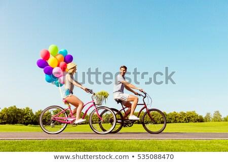 Affectueux couple homme femme vélos ballons Photo stock © NikoDzhi