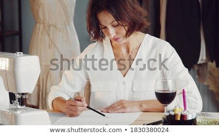 Concentrated woman fashion illustrator sitting at the table. Stock photo © deandrobot