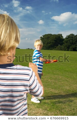 boy throwing frisbee to another boy stock photo © is2