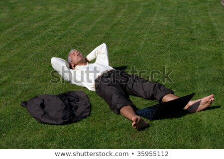 Barefoot businessman lying on grass Stock photo © IS2