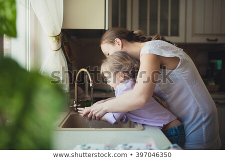 Young woman washing her hands in the kitchen Stock photo © Giulio_Fornasar