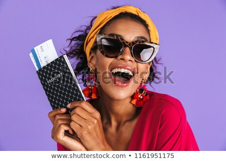 Cheerful african woman in dress and sunglasses holding passport Stock photo © deandrobot