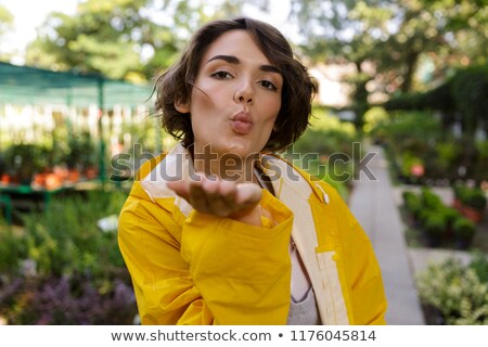 Stock photo: Woman gardener standing over flowers plants in greenhouse blowing kisses.
