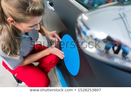 Woman putting sticker with company slogan on a car Stock photo © Kzenon