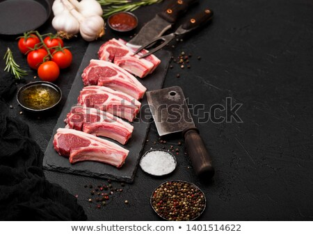 Fresh raw butchers lamb beef cutlets on stone board with vintage hatchet on black stone background.  Stock photo © DenisMArt