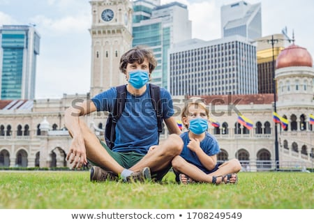 Dad and son on background of Merdeka square and Sultan Abdul Samad Building. Traveling with children Foto stock © galitskaya