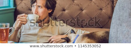 portrait of handsome young man playing with cat and drinks coffee banner long format stock photo © galitskaya
