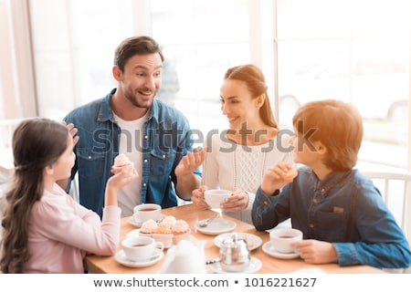 family at coffee house or cafe drinking tea at table stock photo © robuart
