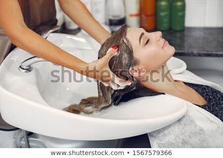 Hairdresser washing hair of client in her shop Stock photo © Kzenon