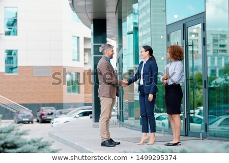One of two young elegant businesswomen handshaking with new colleague Stock photo © pressmaster
