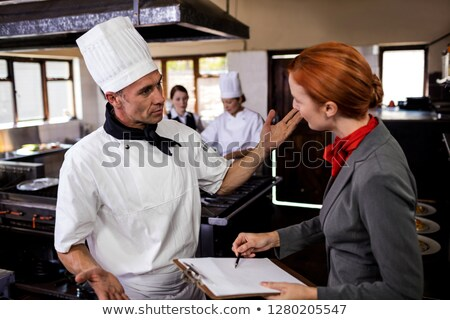 Female manager and male chef interacting with each other in kitchen at hotel Stock photo © wavebreak_media
