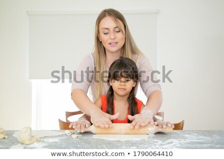 Front view of mother helping her daughter rolling out dough in kitchen at home Stock photo © wavebreak_media