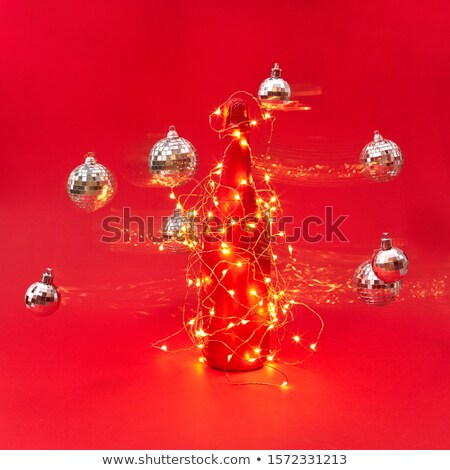 Painted red wine bottle covered Christmas garland with lights. Stock photo © artjazz