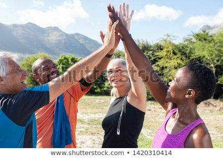 Group of fit friends in the gym giving a high five for motivation Stock photo © Kzenon