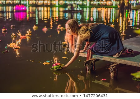 A female tourist holds the Loy Krathong in her hands and is about to launch it into the water. Loy K Stock photo © galitskaya