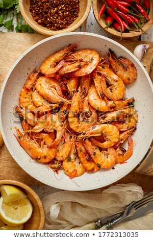 Roasted Prawns on frying pan served on white wooden cutting board Stock photo © dash