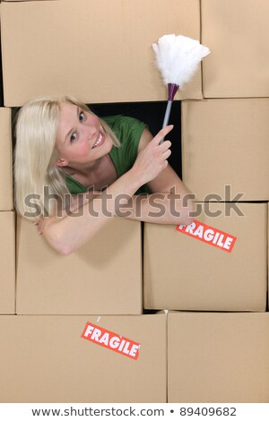 radiant blonde amid cardboard boxes holding feather duster Stock photo © photography33