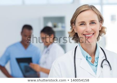 Sorridente feminino médico olhando raio x médico Foto stock © IS2