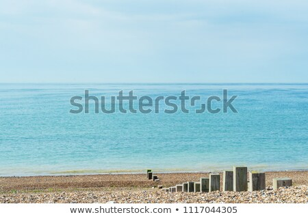 Pebble Beacn with Wooden Posts Leading to Shoreline Stock photo © frannyanne