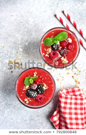Glass of fruit smoothie and fresh berries with oat homemade granola, chia seeds on a wooden board on Stock photo © artjazz