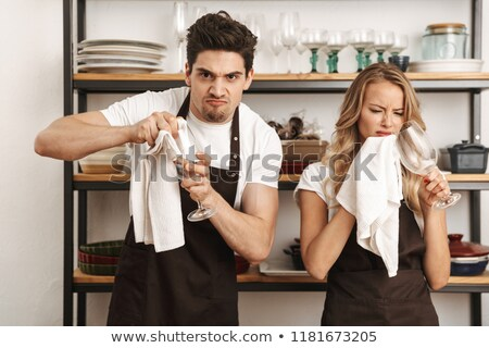 Young friends loving couple chefs on the kitchen wipe glasses. Stock photo © deandrobot