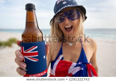 Australian woman holding offering a bottle of beer Stock photo © lovleah