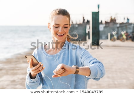 woman with headphones and fitness tracker on beach Stock photo © dolgachov