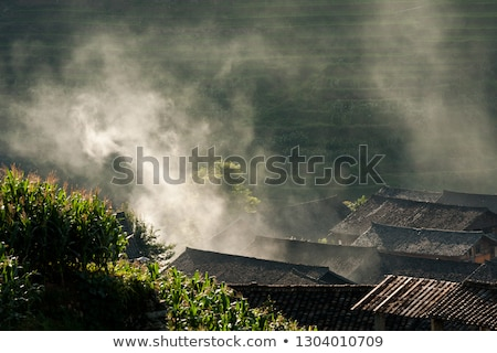 Rooftops and smoke in rice terraces landscape China Stock photo © Juhku