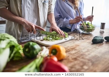 close up of couple cooking food at home stock photo © dolgachov