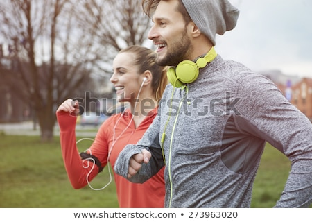 couple with headphones running outdoors stock photo © dolgachov