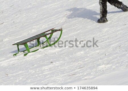 little boy with sled climbing snow hill in winter Stock photo © dolgachov