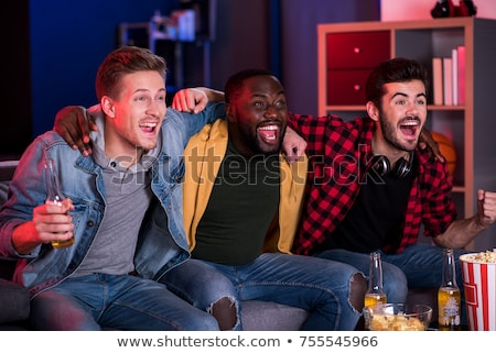 friends cheering while watching sport at home stock photo © andreypopov
