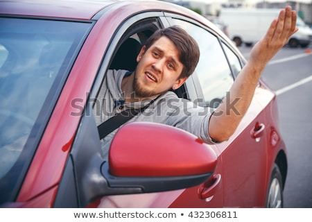 Stock photo: Irritated young man driving a car. Irritated driver